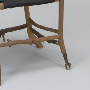 A four leg chair with armrests made of maple branches. The back of the chair is made of farming tools and the seat composed of a weaved black material. Proper front left foot is metal, with decorative talons holding rock-crystal ball.