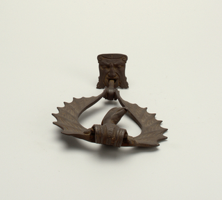 Door knocker. Plate in the form of a grotesque face. Handle is a bird with outstretched wings.