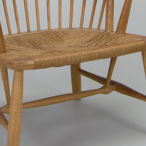 Formed as a slatted back rest fanning out with spindles that resemble peacock feathers framed by a rounded crest rail ending in a rope cord seat.  The legs of the chair splay out slightly and are connected by a stretcher.  Below the seat, two sticks rise up and are continued above by the arm support, where these two elements meet at an acute angle through the arm rests.