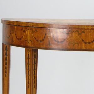 A light wood half table with scalloped edges sitting on three legs. The legs are curvilinear and looped under with added curved wood pieces.