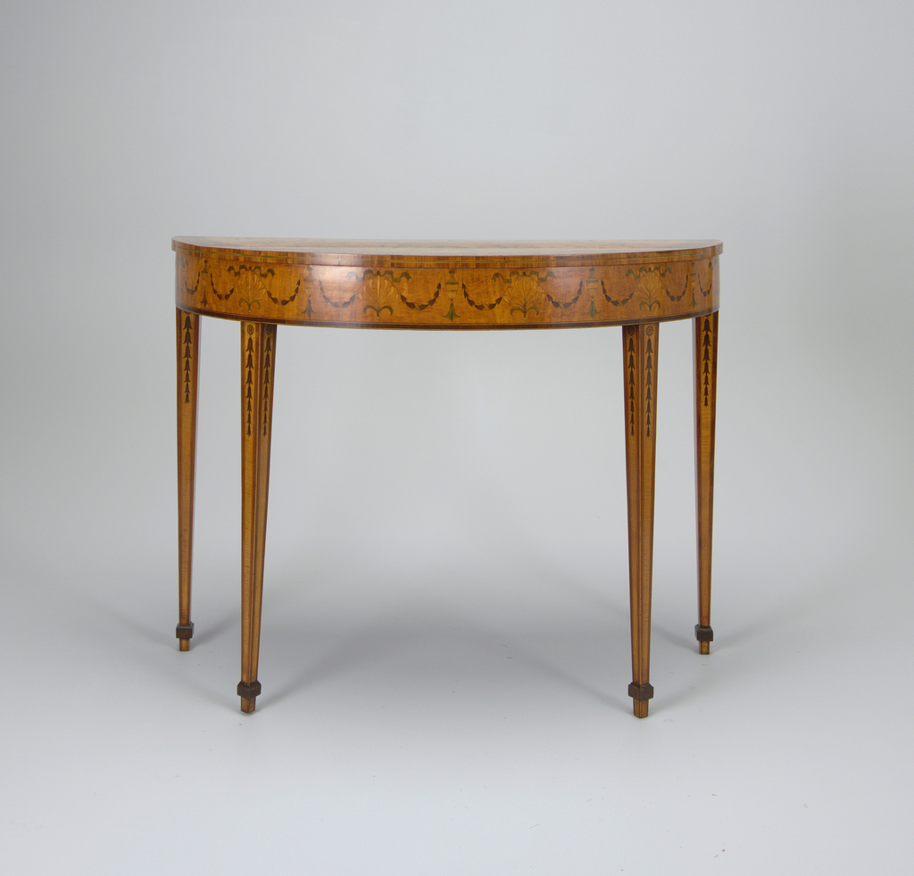 Each of demi-lune form, the top inlaid with ribbon-tied floral garlands set into the satinwood, all centered by a fluted demi-lune, that when the tables are put together becomes a patera; the border all surrounded by a contrasting border of rosettes and attenuated anthemia; the skirt inlaid with swags of husks, anthemia, and urns; the tapered quadrangular legs inlaid with husks.