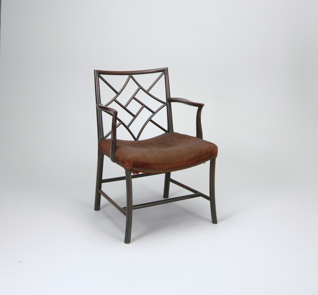 """A side chair with a rectangular back filled with a lattice-work of curved members.  Its curved arms are supported on shaped stumps secured to side rails.  Round rear legs; """"cluster"""" front legs.  Two lateral and two longitudinal stretchers.  Hollowed seat upholstered in brown wool. Described as """"cockpen"""" armchairs."""