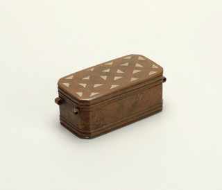 "Rectangular box with hinged lid, chamfered corners, fittings for missing handles at either end. Inlaid pattern of triangles on top, raised bandings around sides, top and bottom. Interior divided into three compartments; the two smaller compartments covered by hinged lids with raised ""X"" decoration."
