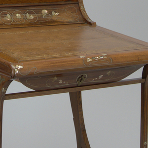 Small writing desk with curved back continuing in natural curve down the back legs. Liftable writing surface inset with stamped leather. Surface on all sides decorated with Oriental design of petals of mother-of-pearl and entwining lines of brass and silver alloy.  Label on drawer edge: Carlo Zen/Milano