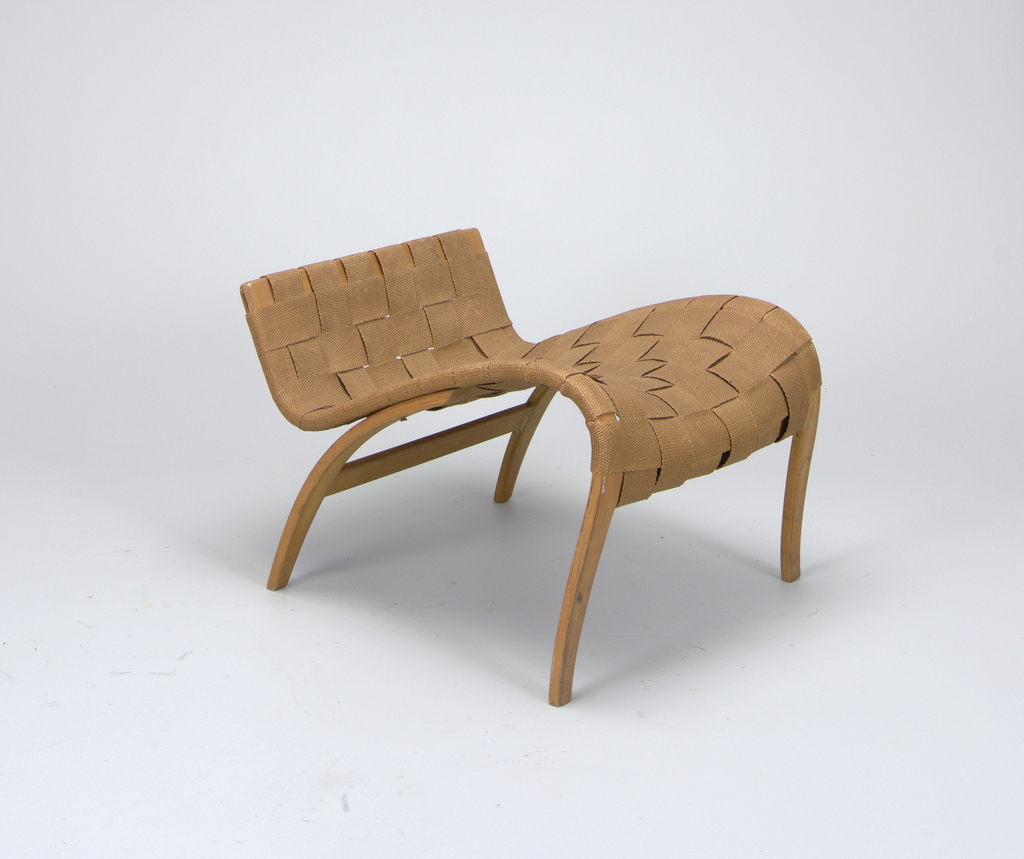 """Shaped, bent birchwood armchair (a), the frame with high contoured back and curved seat, upholstered in tan webbing; short, sinuous bentwood arms; four curved tapering legs.  En suite with ottoman (b), the sinuous bent birchwood frame up-curved at end, upholstered in tan webbing; four curved and canted tapering legs.  Thick, rectangular cushion (c) covered in orange and tan woven fabric in the """"Percybald"""" (Percy Leaf) pattern showing large flowers and leaves."""
