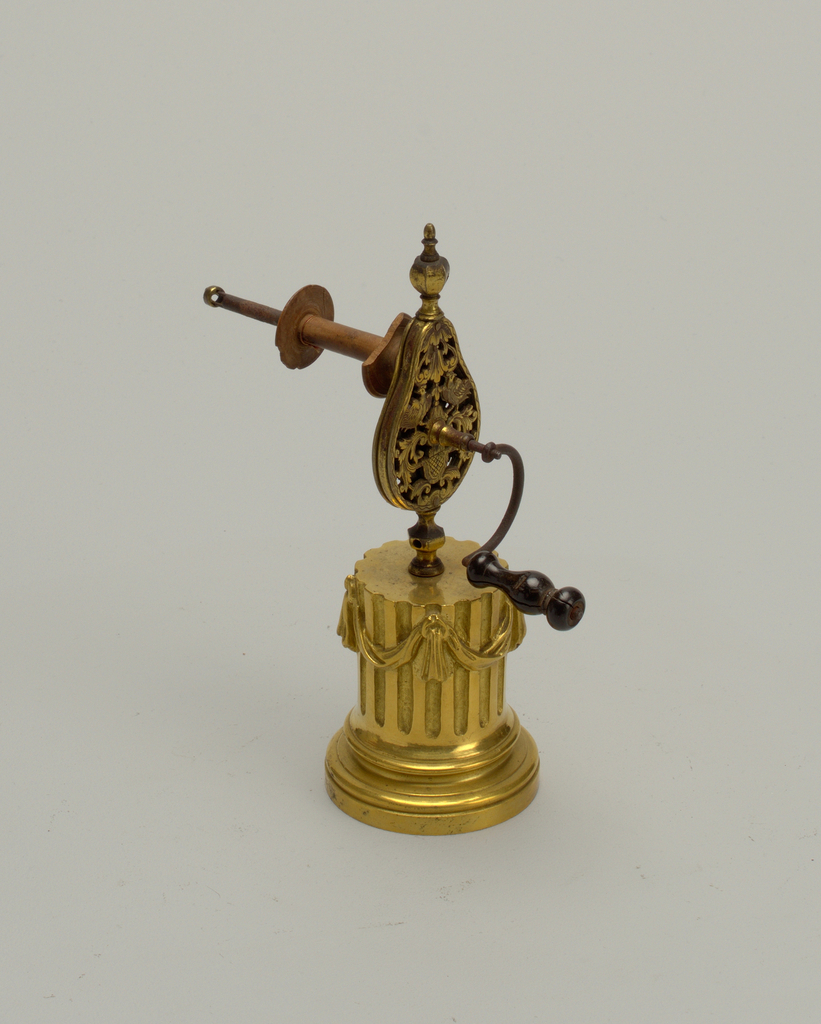 Gilt bronze silk winder. Pear-shaped body with symmetrical motif of cocks on scrollwork. Base in the form of a partial fluted column with drapery. Turned wood handle, the bow-ended base inset with a leather panel.