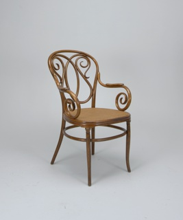 "Bentwood armchair with caned seat, two scrolling armrests, circular ""stretcher"" and four tapered legs.  Armrests on each side terminate in scrolls."
