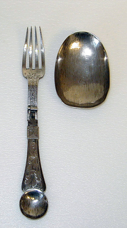 Fork has three curved tines, flat tapering handle with bowl-shaped end, scrolled shoulders. Hinged at neck, faceted sliding lock bar. Octagonal handle with engraved fish-bone decoration and floral design, baluster shaped top.  Oval spoon bowl, engraved on back with symmetrical floral design. Two slots on the back of bowl to attach the fork.