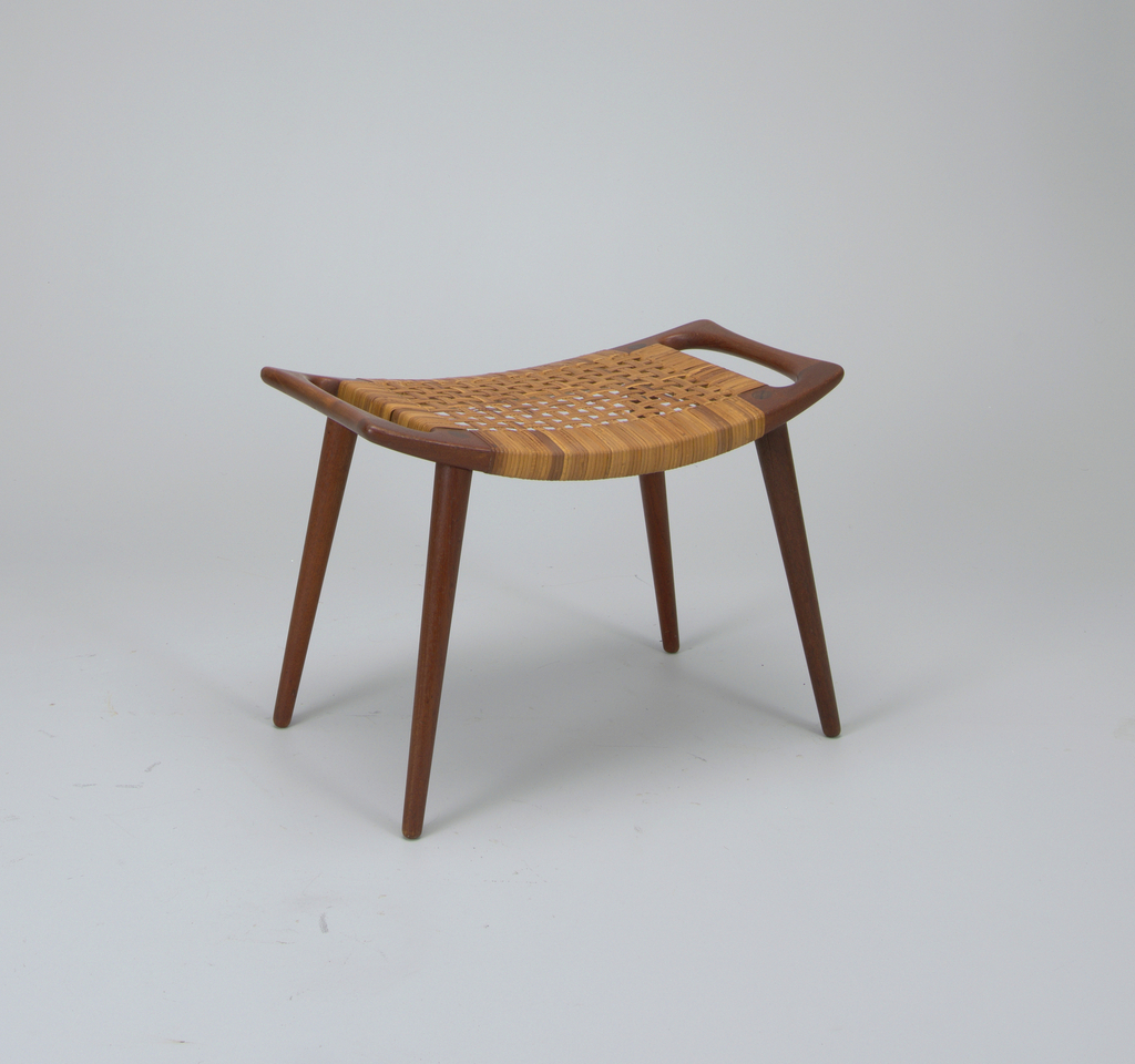 Dark brown up-curved rectangular frame with woven cane seat panel, on four tapered legs.