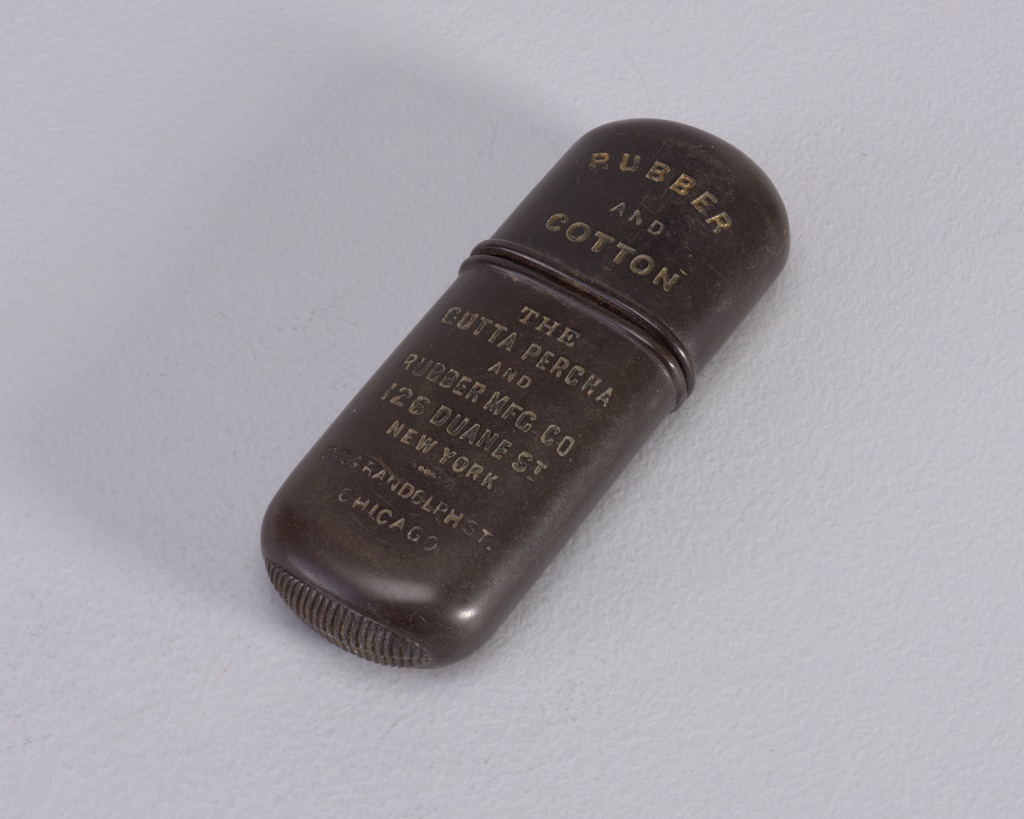 "Elongated oval matchsafe in a dark brown color. One side says ""Rubber and Cotton The Gutta Percha & Rubber MFG. CO. 126 Duane St. New York Randolf St. Chicago"". The reverse side has a cross and says ""Fire Hose hose belting packing vaulves & co."""