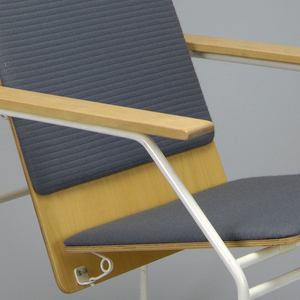 Flat wooden seat and back attached at a convex angle, with surfaces upholstered in fine blue-knit wool.  The chair's supporting tubular steel frame is painted white, including a front and back stretcher.  The armchair has elongated, rectangular armrests, also of laminated wood and surmounted to the steel frame.