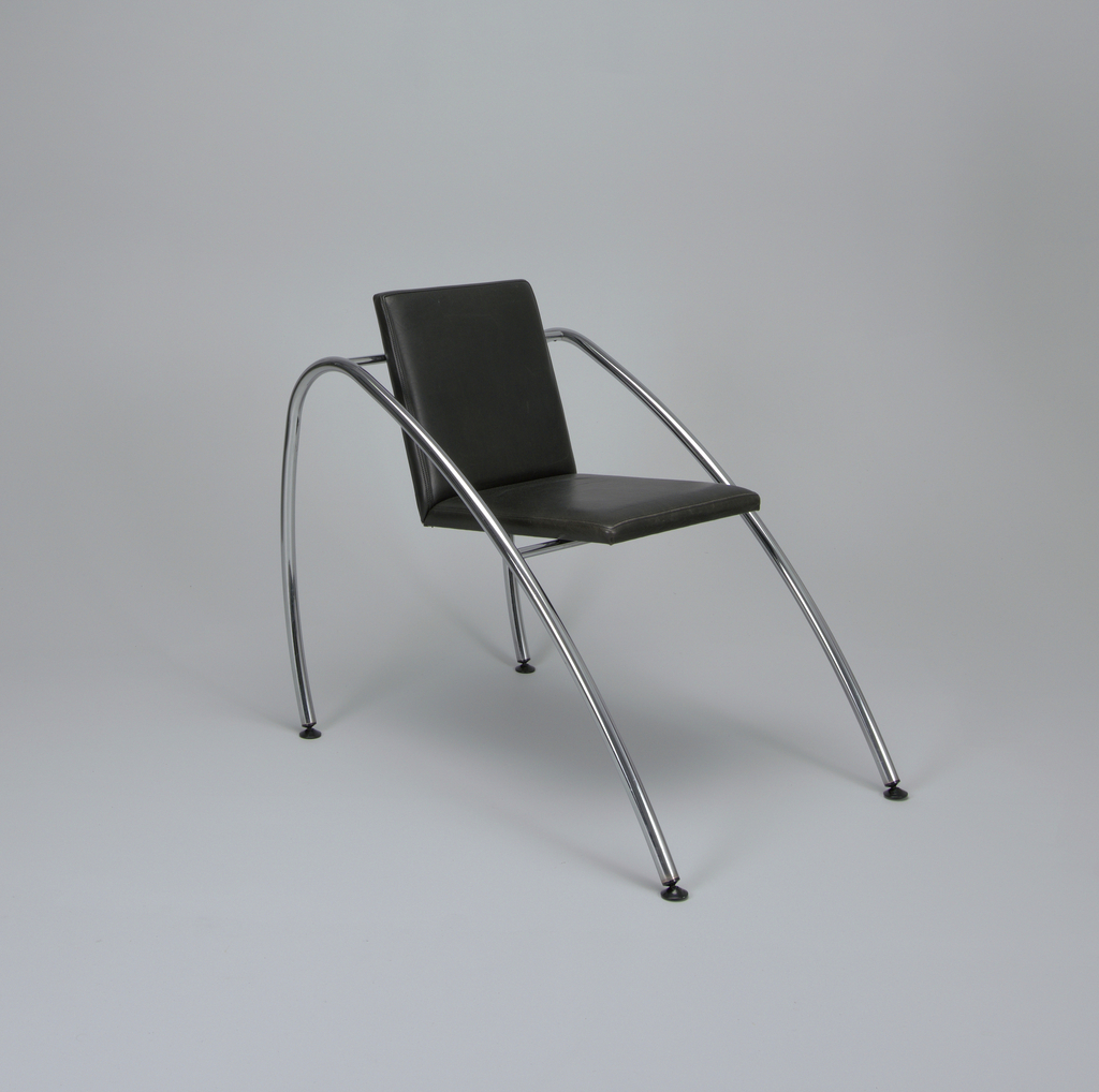 Chair with leather L-shaped seat and back supported by two horizontal steel tubes—one at the back and one under the seat—that are flanked by two skewed steel tube arches, which act as both arms and legs, ending in black plastic casters.