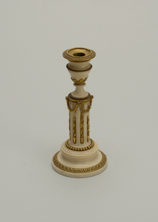 White marble candlestick (a), the urn shaped nozzle with removeable ormolu leaf collar (b), on fluted columnar shaft with ormolu stops; capstan base with leaf tip and bead molding.