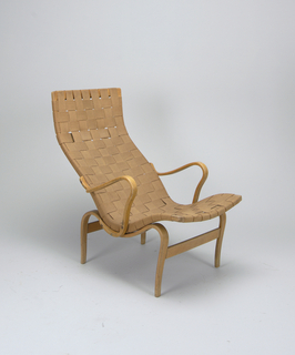 "Shaped, bent birchwood armchair (a), the frame with high contoured back and curved seat, upholstered in tan webbing; short, sinuous bentwood arms; four curved tapering legs.  En suite with ottoman (b), the sinuous bent birchwood frame up-curved at end, upholstered in tan webbing; four curved and canted tapering legs.  Thick, rectangular cushion (c) covered in orange and tan woven fabric in the ""Percybald"" (Percy Leaf) pattern showing large flowers and leaves."