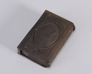 A rectangle matchsafe in a dark brown color. One side in a profile of a woman with a veil and the other side a man.