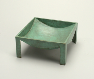A vessel with a square rim, concave bowl and four L-shaped legs. Green allover patin