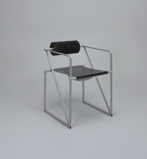 "A pair of cylinders of ribbed, black polyurethane makes up the chair's back.  The chair's sides and ""armrests"" consist of square-shaped enameled steel frames, crossed by a diagonal.  Perforated seat."