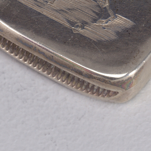 Rectangular, curved corners, featuring incised decoration of male swinging golf club, he wears cap, jacket, knickers, diamond-patterned socks and spats. Lid hinged on side, thumb catch at front. Striker in recessed groove on bottom.