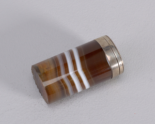 Cylinder in form, single piece of brown agate with white striations, hollowed out to form box; capped with silver collar, silver lid attached to collar, hinged at back; fine band of twisted silver wire wraps around the perimeter of lid's edge, flower with petals of twisted wire at lid's center. Striker carved into stone on bottom.