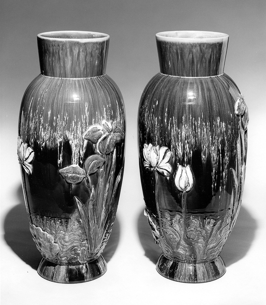 """Red earthenware body. Elongated ovoid shape, flared foot, flared """"collar"""" neck. Body applied with molded iris with purple glaze, and white water lilies, both with foliage emerging from stylized water lines. Body glazed in striated brown, green and white, with surface iridescence. Interior glazed."""