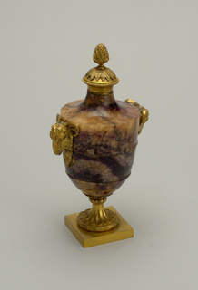 Amphora-shaped body of solid spar supported on fluted pedestal on square base. Pedestal, top and mountings of gilt gold bronze. Top is an artichoke rising from a circular cluster of leaves. Two ram's heads at shoulder, on either side.