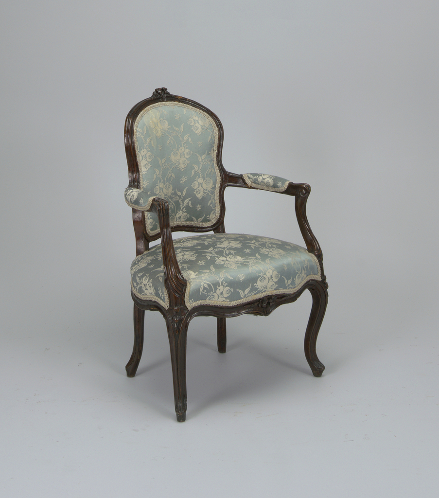 Upholstered rounded channeled back crested with carved spray of two flowers - curved padded arms - shaped rails frame upholstered seat, channeling conturned into the cabriole front legs - front rail carved similarly as cresting cabriole rear legs.