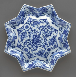 Eight-pointed star-shaped plate, raised rim; painted in underglaze blue on white, with dark outlines (trek), center medallion with dragon in reserve, surrounded by floral reserves, cavetto and rim with border of dragon heads in reserve against diaper and leaf pattern; bottom low foot rim, 2 bands blue.