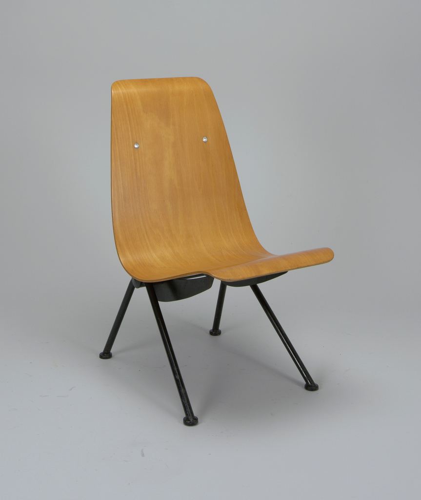 Seat and back formed of single curved sheet of laminated plywood, mounted on black-enameled metal frame consisting of flat boomerang-shaped supports on cylindrical strut and A-frame tubular metal legs.