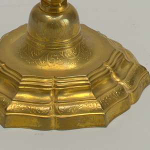 Candlestick with wide base decorated with engraved scrolls. Hexagonal candle socket
