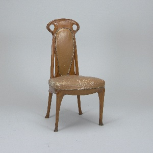 Tall slender back pierced at sides of crest rail where handle-like openings are formed, and at sides of back. Four slender legs. The whole with long curvilinear elements which resolve at sides of crest rail and mid-points of posts into finely carved semi-abstract scrolls and foliations; back and seat covered in tan leather upholstery secured at edges with circular and lozenge-shaped brass nails; spring seat.