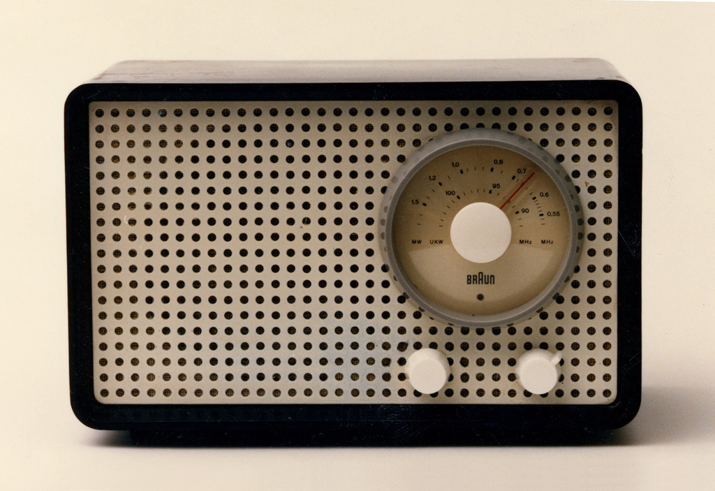 A rectangle front faced radio with one large tuner dial and two smaller knobs on the right and the speaker on the left. The front including the speaker is covered with a whole punched pattern plastic.