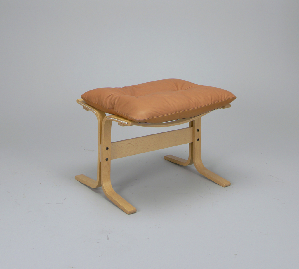 Bent beech wood legs with horizontal bar; honey brown leather cushion resting atop.
