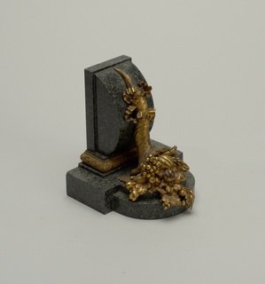 Pair of bookends (a & b). Each architectonic, L-shaped, stepped and curved green/black granite base with applied gilt bronze cornucopia, be-ribboned and spilling forth fruit, foliage and flowers; three-sided, rectangular band of gilt bronze molding just below joint of vertical and horizontal granite elements.