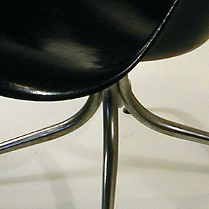 Chair seat and back of contoured, molded dark grey fiberglass: curved, oval back on tubular steel frame mounted on concave seat with out-curved sides forming armrests; tubular steel base splayed to form four curved legs terminating in circular foot pads.