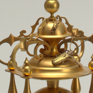 Four-legged gold decorative clock with the center circle part of the clock in between legs, and a raised dome top. The insects replace the numbers and the arms on the clock as well as a few scattered among other parts of the sculpture.