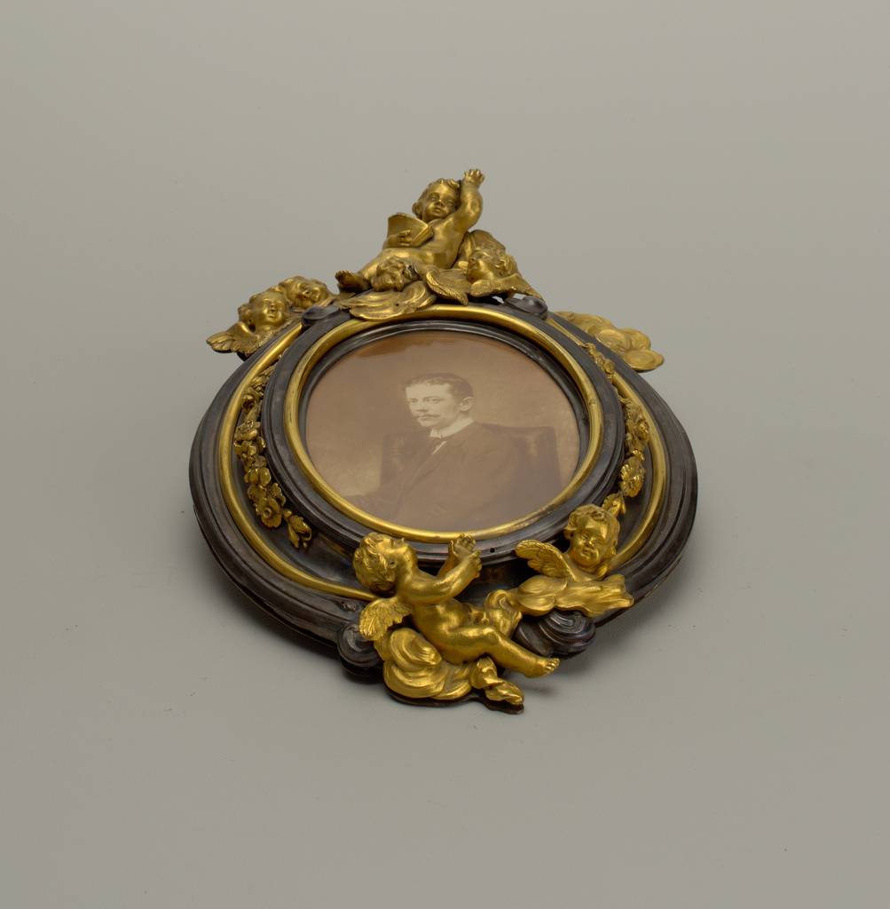 Frame, easel Oval frame with bronze cupids at top - easel