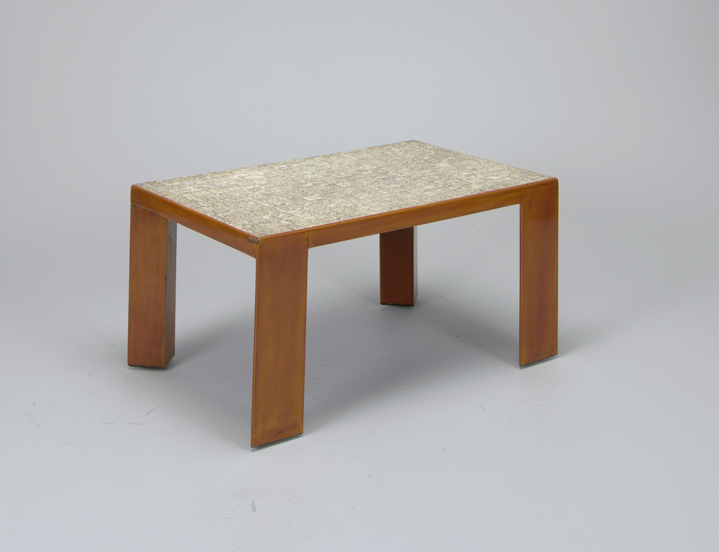 Low rectangular wooden table with triangular legs; table top decorated with coquille d'oeuf (crushed egg shell); legs and vertical surfaces finished with caramel-colored lacquer.