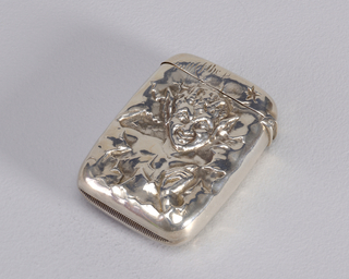 "Rectangular, rounded corners and sides, featuring raised relief of devil poking his head and hand through a jagged or torn edged reserve, inscribed ""Full of the D"" on upper left of lid, just above his head. Reverse features raised relief of hand bursting through small torn edged reserve, clutching three burning matches, also visible is devil's tail bursting through  area to the upper-left of hand, interwined around the matches. Lid hinged on side. Striker in recessed groove on bottom."