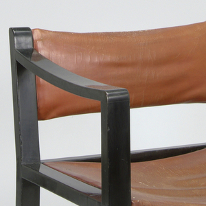 This armchair has a squared-off frame and a slightly raked back.  The chair's arms curve slighty upward towards the back.  The chair's members are rectangular in all sections and the entire frame is in black lacquer.  The chair's back and seat, slung from the frame, are of brown calf leather.  The seat and back are in reddish-orange leather.