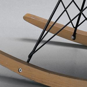 Light yellow bucket seat surmounting criss-crossed metal rod legs on curved wooden rockers.