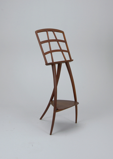 Three-legged hand-carved wood music stand with bottom triangular shelf and open lattice-work top to rest sheet music upon.