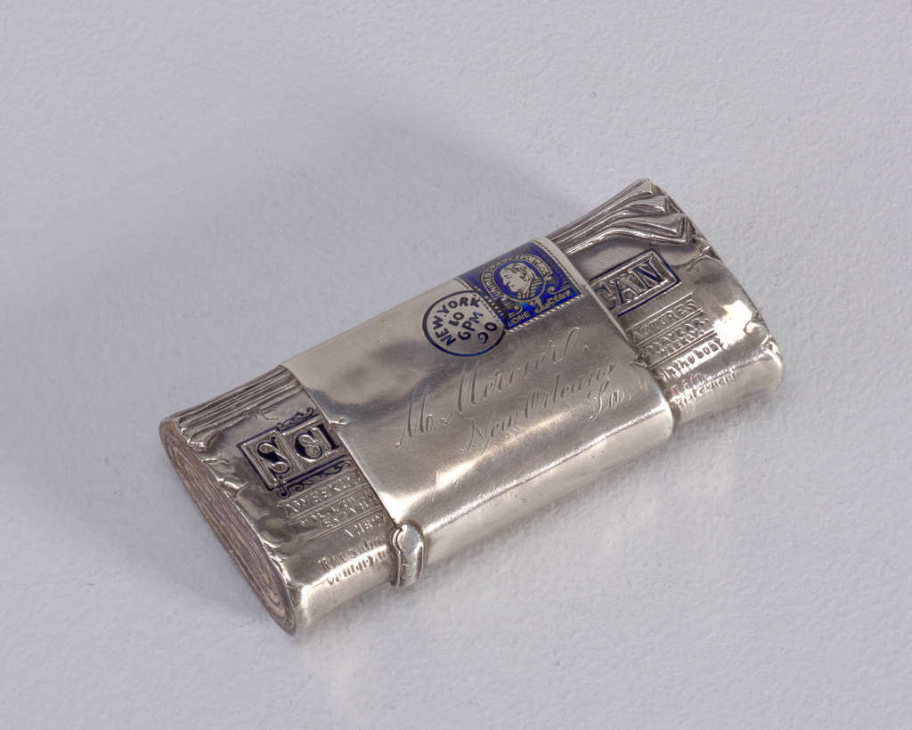 A silver colored matchsafe in the form of a newspaper with a letter on top.