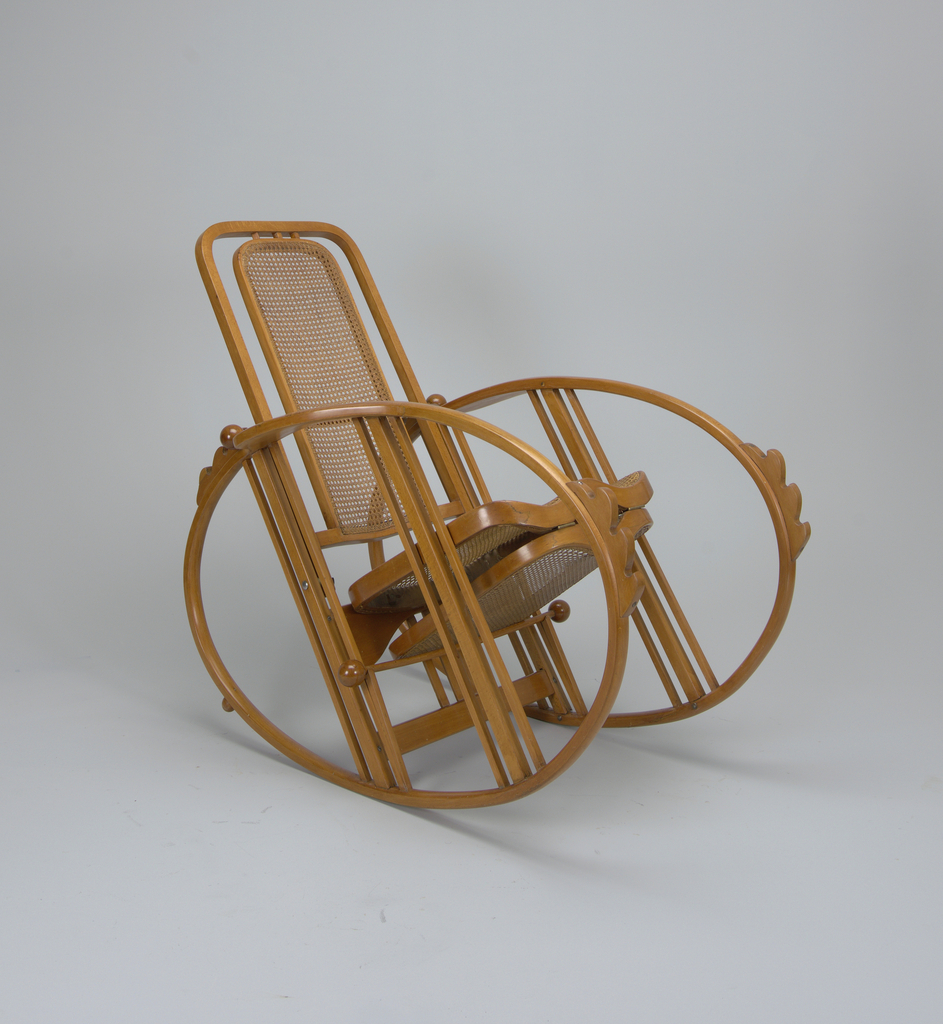 An adjustable reclining rocking chair made of bent beechwood with woven cane back, seat, and foot rest, hinged to fold under seat. The chair sits on two ovals which serve as its arms and rockers.