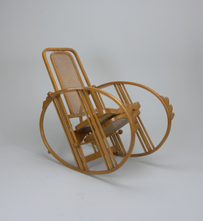 A reclining rocking chair made of bent beechwood. The chair sits on two ovals which serve as the chair's feet.