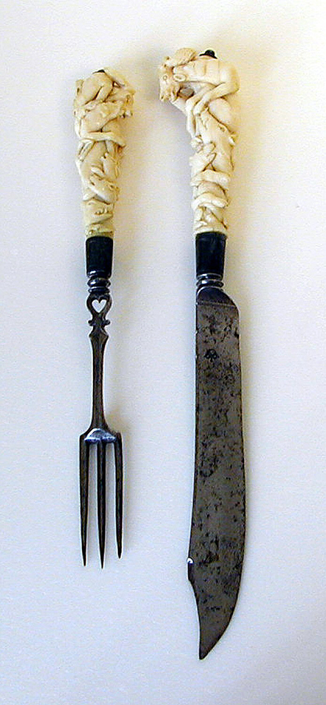 Scimitar-shaped blade, curved cutting edge upturned tip. Baluster neck, silver ferrule with engraved border. Ivory handle carved in deep relief with entwined hunting dogs and prey: stag, boar, rabbit. Button cap at end of handle.