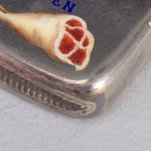 """Rectangular, rounded corners, featuring word/picture rebus """"Tis [Rare] That We May Often [Meat]"""",  with sides of beef, enameled in red and white, as substitutes for words """"rare"""", and """"meat"""", """"meat"""" being a play on """"meet"""", text enameled in blue, with first letter of each word in red. Lid hinged on left, small protruding thumb catch on right. Striker in recessed groove on bottom."""