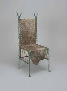 Textured green and black iron frame with a single piece of hide stretched and laced to the frame with red cord along the edges; cord laced on left and right below seat; tall back surmounted by pair of small metal horns at top left and right.
