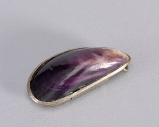 "In the form of a mussel shell, with real shell mounted into silver frame on top, silver container attatched to underside, surface of which features incised  floral decoration and inscribed ""J.Reed, Xmas 1902, "" decorated surface flips open to reveal match compartment. Link attached to narrow end. Striker on side."