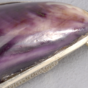 """In the form of a mussel shell, with real shell mounted into silver frame on top, silver container attatched to underside, surface of which features incised  floral decoration and inscribed """"J.Reed, Xmas 1902, """" decorated surface flips open to reveal match compartment. Link attached to narrow end. Striker on side."""