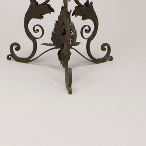 A scrolling vegetal tripod base supports a straight stem with a baluster detail at center. At top, painted flowers and leaves support a scalloped yellow plate.